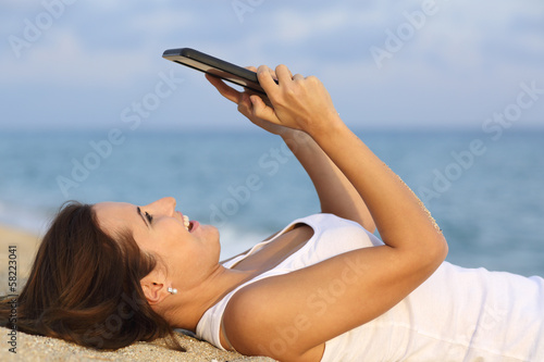 Side view of a teenager girl browsing her tablet pc