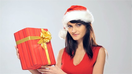 A young woman in a Christmas hat holding a present
