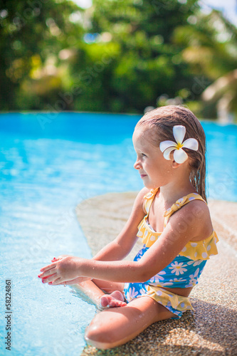 Adorable girl with flower behind her ear sits near swimming pool