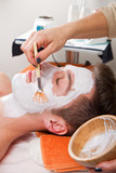 Therapist applying a face mask to a beautiful young man in a spa