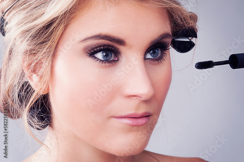 Closeup of Girl applying Eye Makeup.
