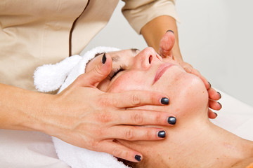 Beautiful young woman receiving facial massage with closed eyes