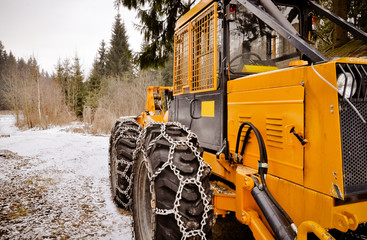 Big forest vehicle with snow chains on the wheels