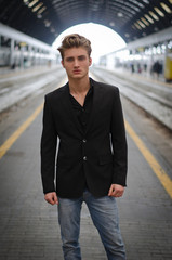 Attractive blue eyed, blond young man standing in train station