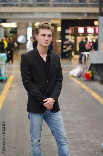 Handsome blond young man standing in station or shopping center