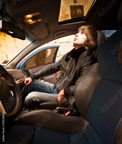 man sitting on passenger seat and looking in sunroof glass