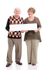 senior couple holding white board