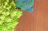 Raw broccoli and romanescu vegetables, on wooden background