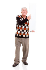 old man pointing at white board