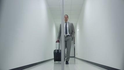 business man walking in corridoor of office building with trolle
