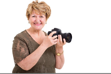 senior woman holding a digital SLR camera