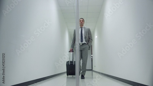 business man walking in corridoor of office building with trolle