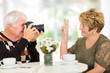 elderly man photographing his wife