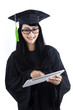Woman in graduation gown using a tablet