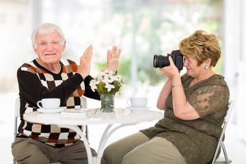 senior man refusing to be photographed