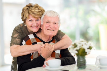 retired couple hugging at home
