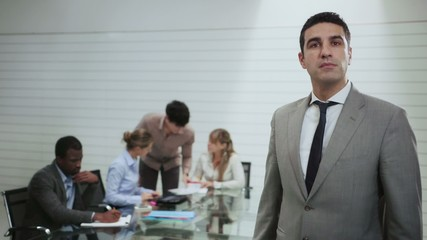 portrait of man with business people in office meeting room
