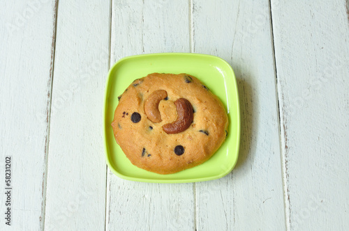 Almond-cookie on green plate on wood table.