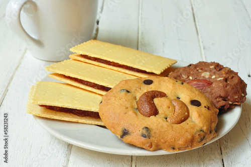 Various crackers, cookies on plate with coffee on wooden table.