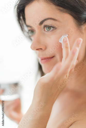 woman in her forties applying cream