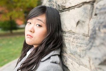 Sad woman by a stone wall