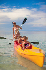 Two little girl and young mother kayaking at blue warm sea