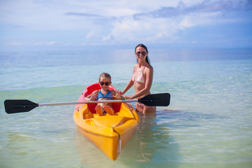 Young mother and two her little daughters kayaking at tropical