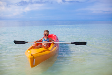 Little cute girl rowing a boat in blue clear sea