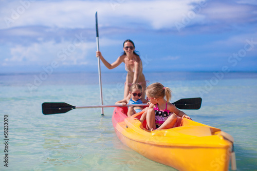 Two little girl and beautiful mother kayaking at tropical warm