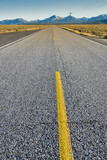Lonesome highway with yellow lines and mountains poster