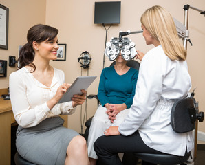 Ophthalmologists Examining Senior Woman In Store