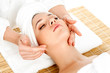 Woman getting facial massage in spa salon