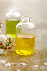 Two massage oil with spring flower on old wood