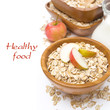 oat flakes with apples in a wooden bowl and a jug of milk