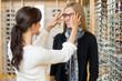 Leinwanddruck Bild - Salesgirl Assisting Customer To In Wearing Glasses