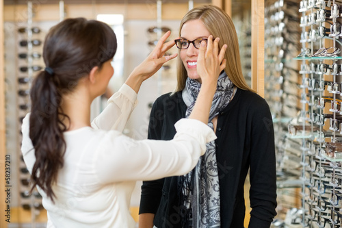 Salesgirl Assisting Customer To In Wearing Glasses