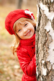 smiling little girl playing hide and seek