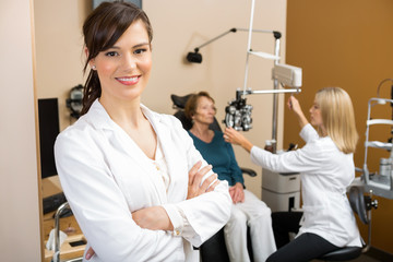 Eye Specialist With Colleague Examining Patient