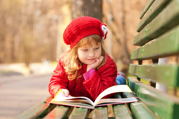 Happy smiling little girl reading interesting book