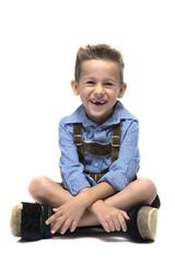 Junge mit Lederhose lacht mit Zahnlücke