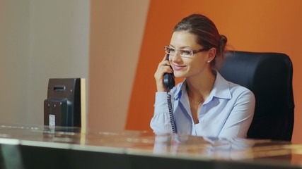 female operator in hotel reception talking on the phone