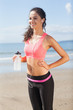 Beautiful smiling healthy woman holding water bottle on beach