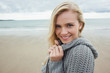 Cute smiling young woman in gray knitted jacket on beach