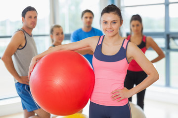 Instructor holding exercise ball with fitness class in backgroun