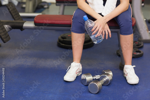 Low section of a tired and thoughtful woman in gym