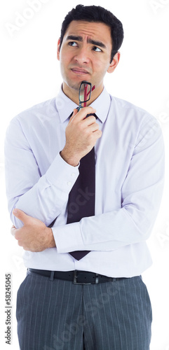 Thinking businessman holding glasses