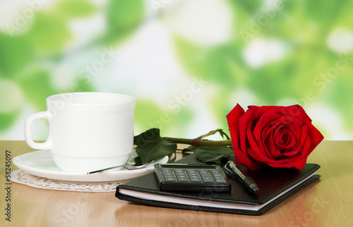 Table in cafe with a cup of coffee, rose and notebook