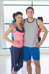 Fit couple with friends standing in background in exercise room