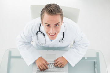 Overhead portrait of a smiling doctor using laptop