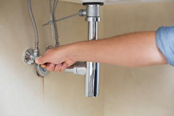 Close up of a plumber repairing washbasin